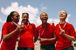 Woman football team with medals celebrating a win. Excited woman soccer team shouting in joy after winning the championship.