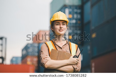 Woman Foreman in hardhat and safety vest holding clipboard checklist and two-way radio aat containers cargo Stok fotoğraf ©