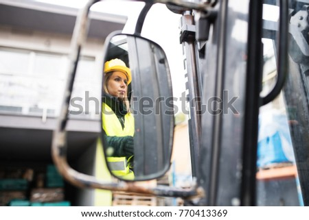 Woman forklift truck driver in an industrial area. #770413369