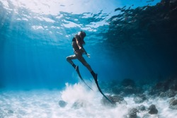 Woman freediver glides with sand over sandy bottom. Freediving underwater in Hawaii island