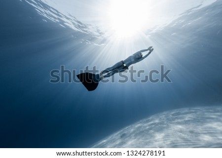 Woman freediver in monofin glides in the depth over the sandy bottom with sunny rays shining through the water
