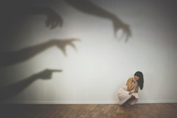 woman frightened by the shadows of hands of demons