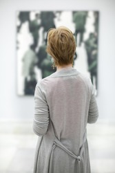 Woman from behind contemplating a pictorial work in a museum in Valencia, Spain