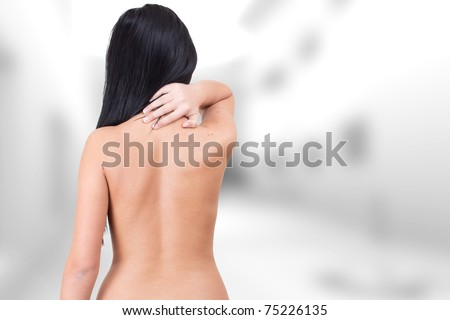 Woman from behind, naked body, holding her neck .