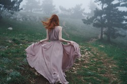 Woman from the back in a pink dress runs through the forest in foggy weather