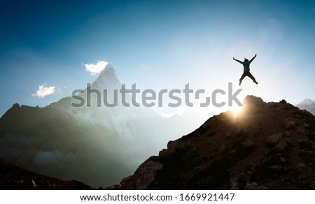 Woman full of joy jumping up on top of the mountain Photo stock ©