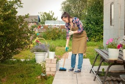 Woman gardener in an apron and gloves sweeps the path with a broom in her garden. A young girl takes care of her dacha plot. Working in her garden near house.