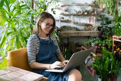 Woman gardener in glasses wear blue jeans overalls, sitting on chair in greenhouse, using laptop after work, communicates on internet with customer surrounded by plants. Home gardening, freelance.