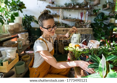 Woman gardener in orange overalls watering potted houseplant in greenhouse surrounded by plants and pots, using white watering can metal. Home gardening, love of plants and care. Small business.