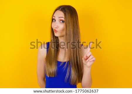 Woman gesturing a no sign. Closeup portrait unhappy, serious girl raising finger up saying: oh no you did not do that. Standing over yellow background. Negative emotions facial expressions, feelings. Foto stock ©