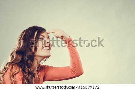 Woman gesturing with finger on her head. Are you crazy? Girl mocking laughing at somebody. Instagram filtered.