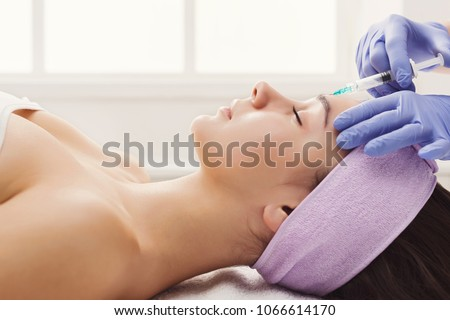 Woman gets beauty facial injections. Anti-aging, nourishing, vitamins treatment at spa salon. Aesthetic cosmetology, side view Foto stock ©