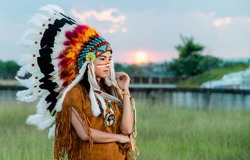 woman gets dressed up as native American Indian. She wears a feathered headdress and has a painted face. Indian woman hunter in concept