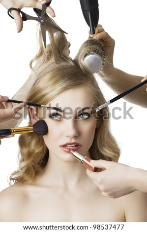 woman getting a beauty and hair style in the same time with hands making differente works, she is in front of the camera and looks up at right