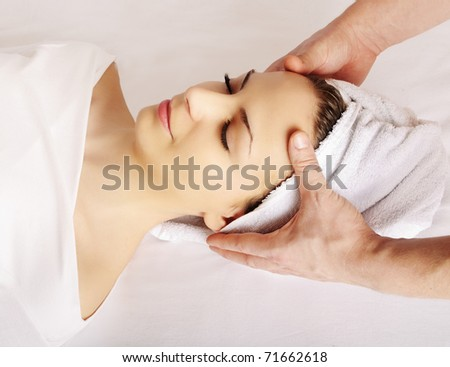 Woman getting a face massage at spa