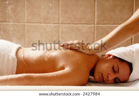 Woman getting a water massage in a day spa