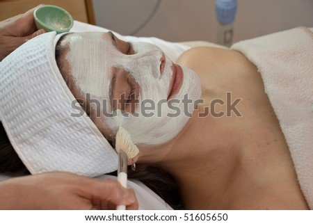 woman getting a white facial mask painted in spa