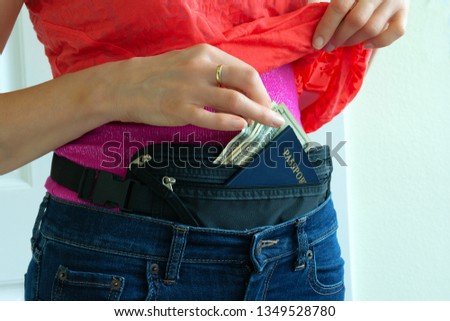 Woman getting cash and passport from hidden travel money belt she has under her clothes to protect herself from pickpocket thieves and credit card scanners safely transporting documents in transit.