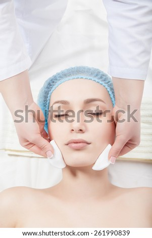 Woman getting face treatment in medical spa center, cleansing with cosmetic cotton pads