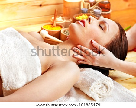 Woman getting facial  massage in wooden spa.