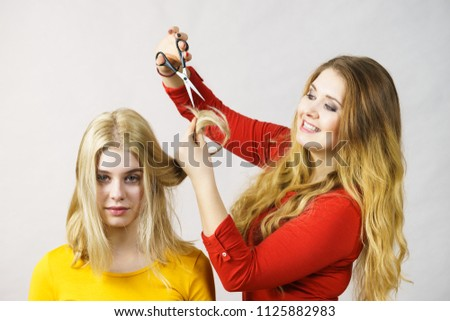 Woman getting haircut from her unprofessional friend using scissors cutting split ends having fun time.