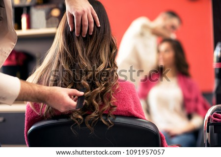 woman getting her hair done in...