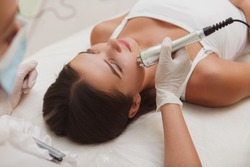 Woman getting rf-lifting facial by professional cosmetician