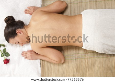woman getting spa treatment. one red rose and bamboo background
