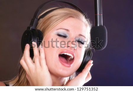 woman girl is singing rock song with a microphone headphones
