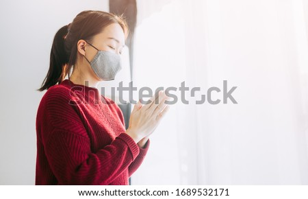 Woman girl stay at home wearing face mask for protect coronavirus covid-19.Prayer girl worship god and pray from home for coronavirus crisis.Pray at home, Church online, Praying hands, Worship at home
