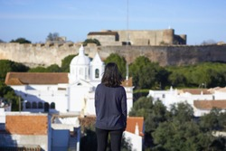 Woman girl traveler looking at Castro Marim church view in Algarve, Portugal with the castle on the background