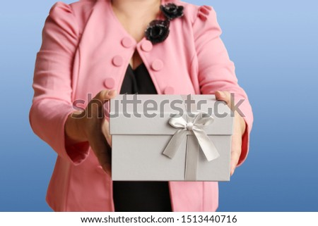 woman gives a present in a light gray box with a satin ribbon and bow, concept of valentines day, christmas presents, mother's day, new year, close-up, copy space