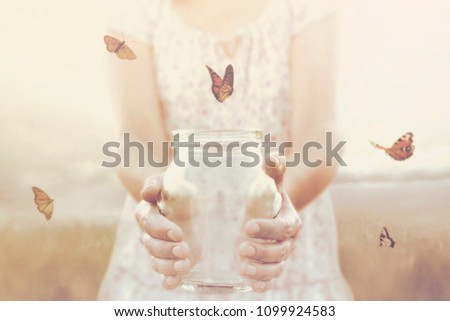 woman gives freedom to some butterflies enclosed in a glass vase
