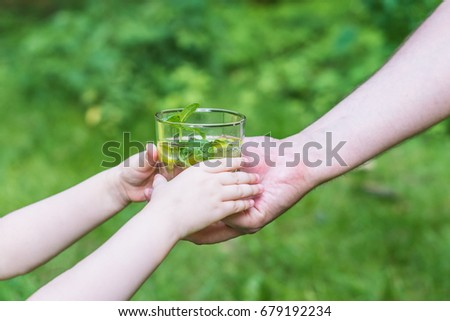 Woman giving a glass of clean water to a child. Green background. - Shutterstock ID 679192234