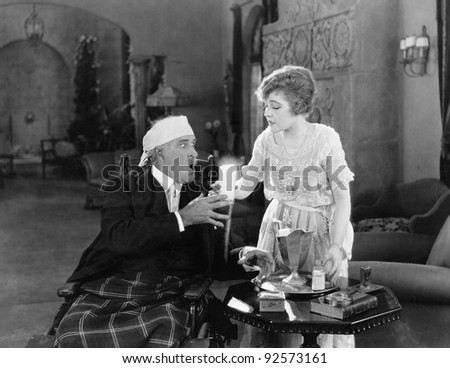 Woman giving a glass of potion to a sick man
