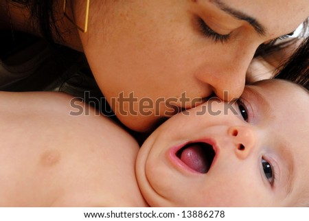 Woman giving a kiss in the baby .