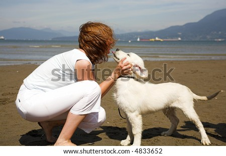 woman giving a kiss to her dog on the beach