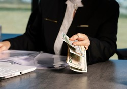 Woman giving bunch of money banknotes, cash back refund, isolated indoors office background. Cropped photo of Business lady in business suit handing dollars bills, focus on hand. Blurred background