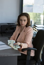 Woman giving bunch of money banknotes, cash back refund, isolated indoors office background. Business lady in business suit handing dollars bills, focus on hand. Woman gives money dollar