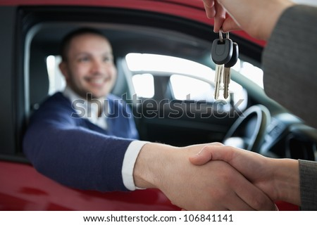 Woman giving car keys while shaking hand in a dealership
