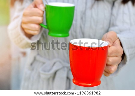 Woman giving cup of hot drink to close person- her boyfriend  family member or friend . Enjoying the moment of loving the same things.Precious moments #1196361982