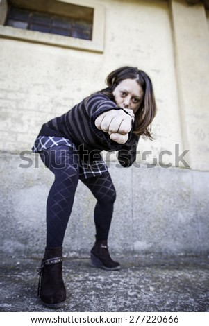Woman giving fist aggressively urban street