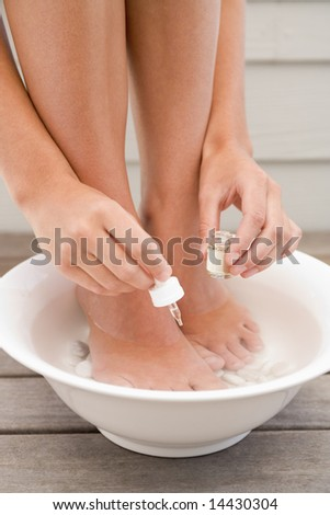 Woman giving herself pedicure