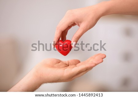 Woman giving red heart to man on blurred background, closeup. Donation concept