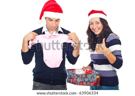 Woman giving thumbs up and smiling  while her husband being surprised of his Christmas gift isolated on white background