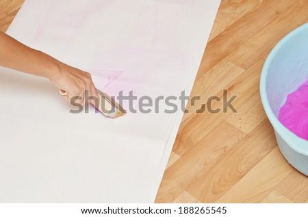 woman gluing wallpaper on the floor