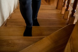 woman going down wooden designer stairs