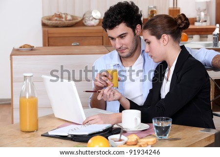 Woman going over a work presentation with her boyfriend during breakfast