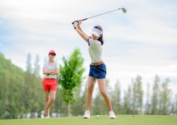 woman golf player in action being setup address of back swing to hit the golf ball away from T-OFF to the destination on the green, fairway at day light sky, PAR 3 T OFF