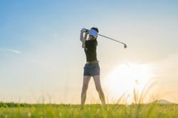 woman golf player in action being setup to hit the golf ball away from fairway to the destination green off, fairway at light of sunset